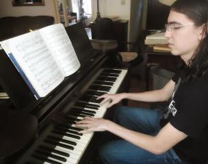Muchacho ensayando en el piano